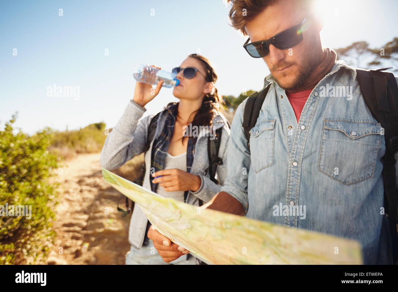 Par el país caminar juntos, vacaciones de verano en el campo. Joven leyendo un mapa, mientras que la mujer Imagen De Stock