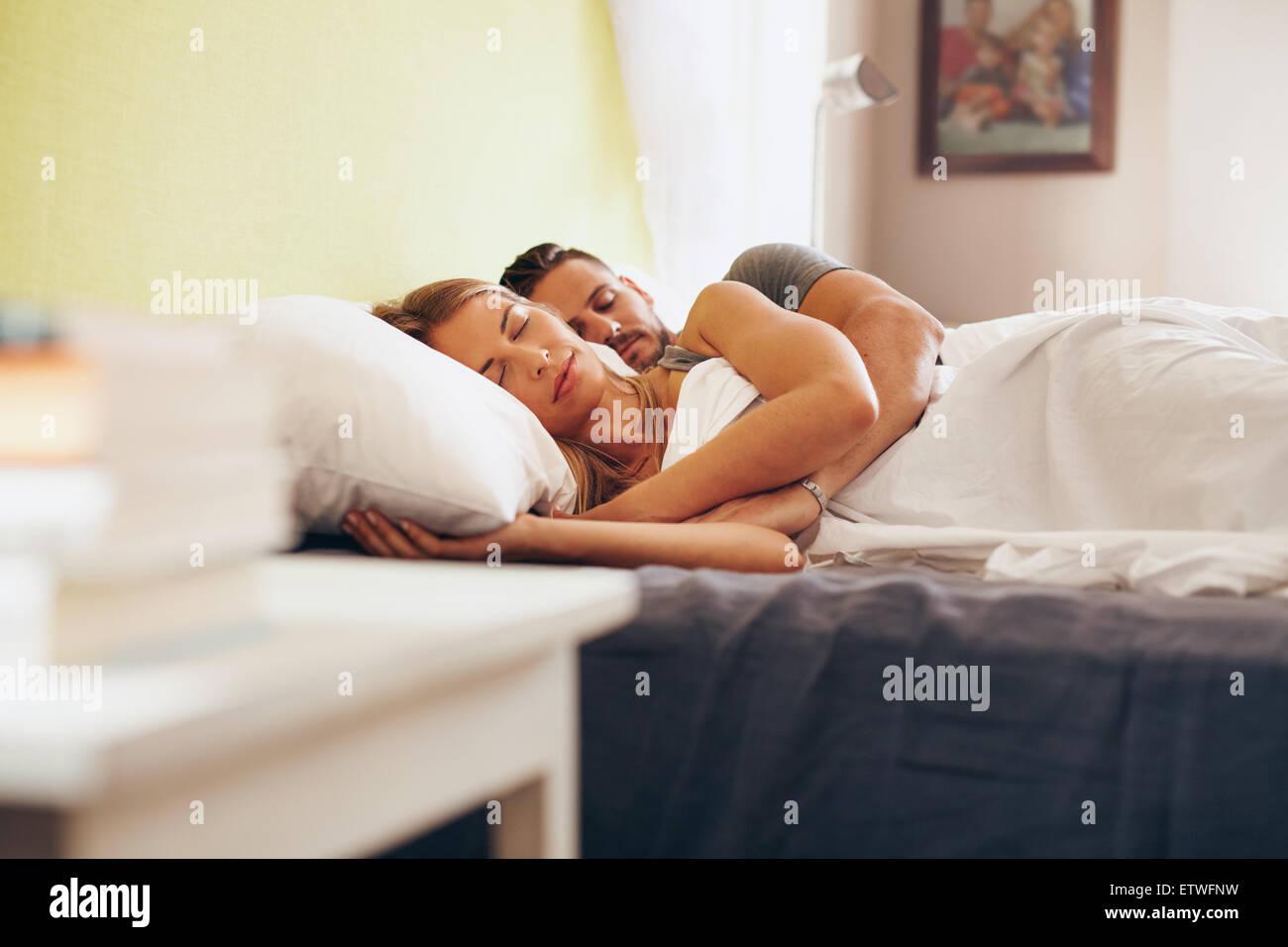 Adulto joven pareja durmiendo pacíficamente en la cama en el dormitorio. Joven Mujer abrazando mientras yacía Imagen De Stock