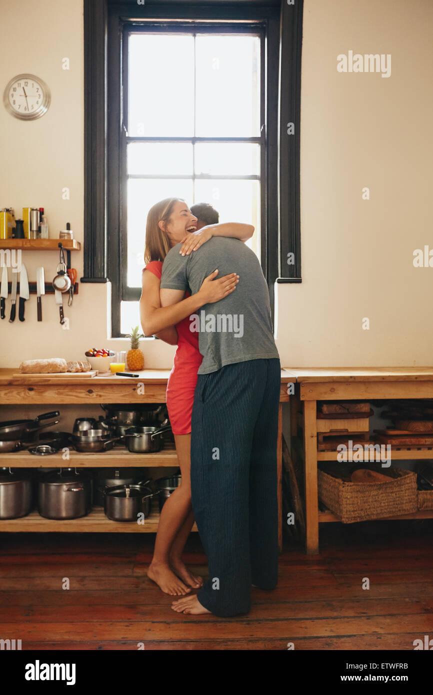 Feliz joven ser abrazados por su novio en la cocina. Alegre joven pareja abrazándose entre sí mañana en casa. Foto de stock