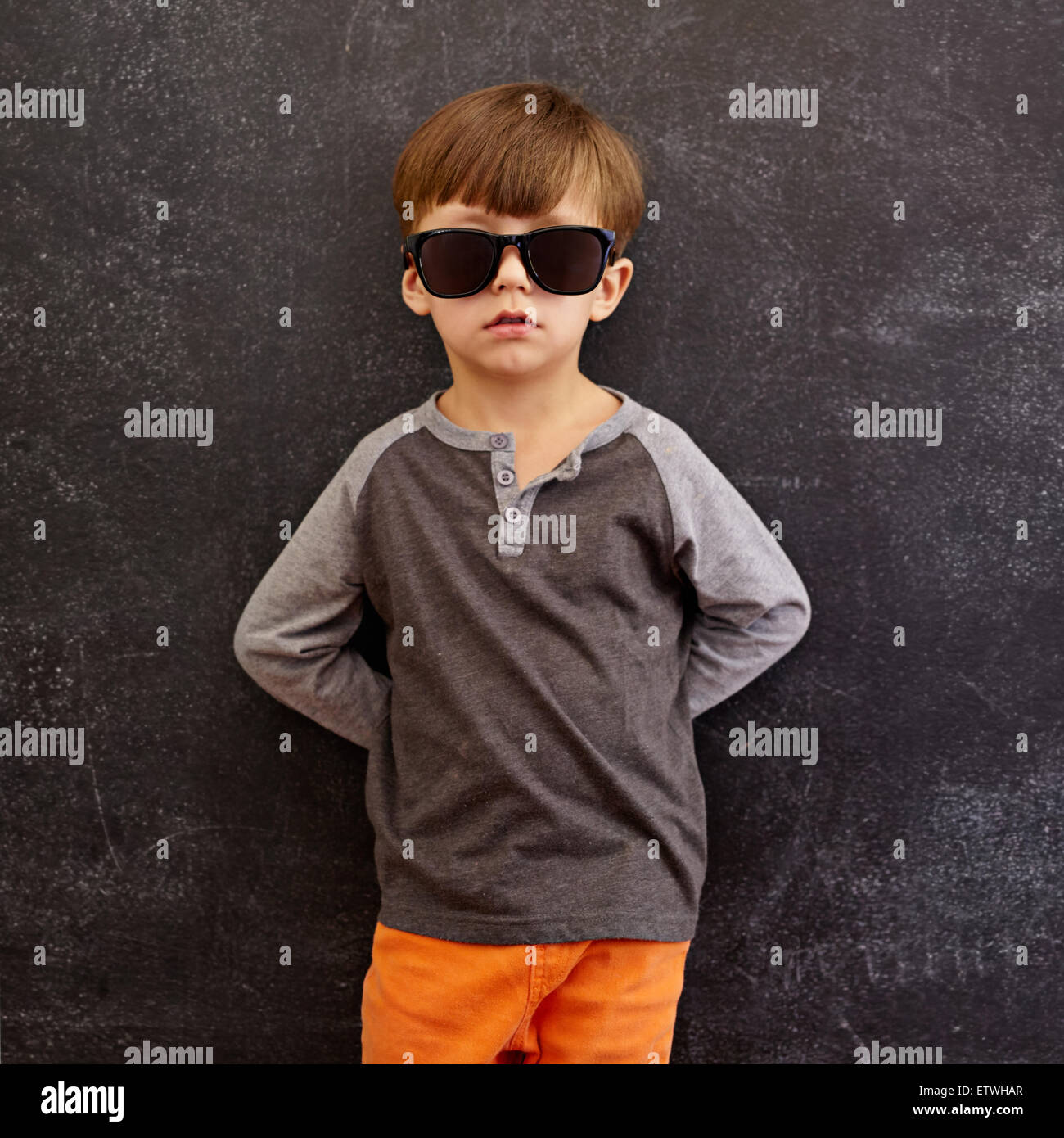 Retrato de niño inocente con gafas de sol. Niñito recostado en una pizarra. Composición de cuadrados. Imagen De Stock
