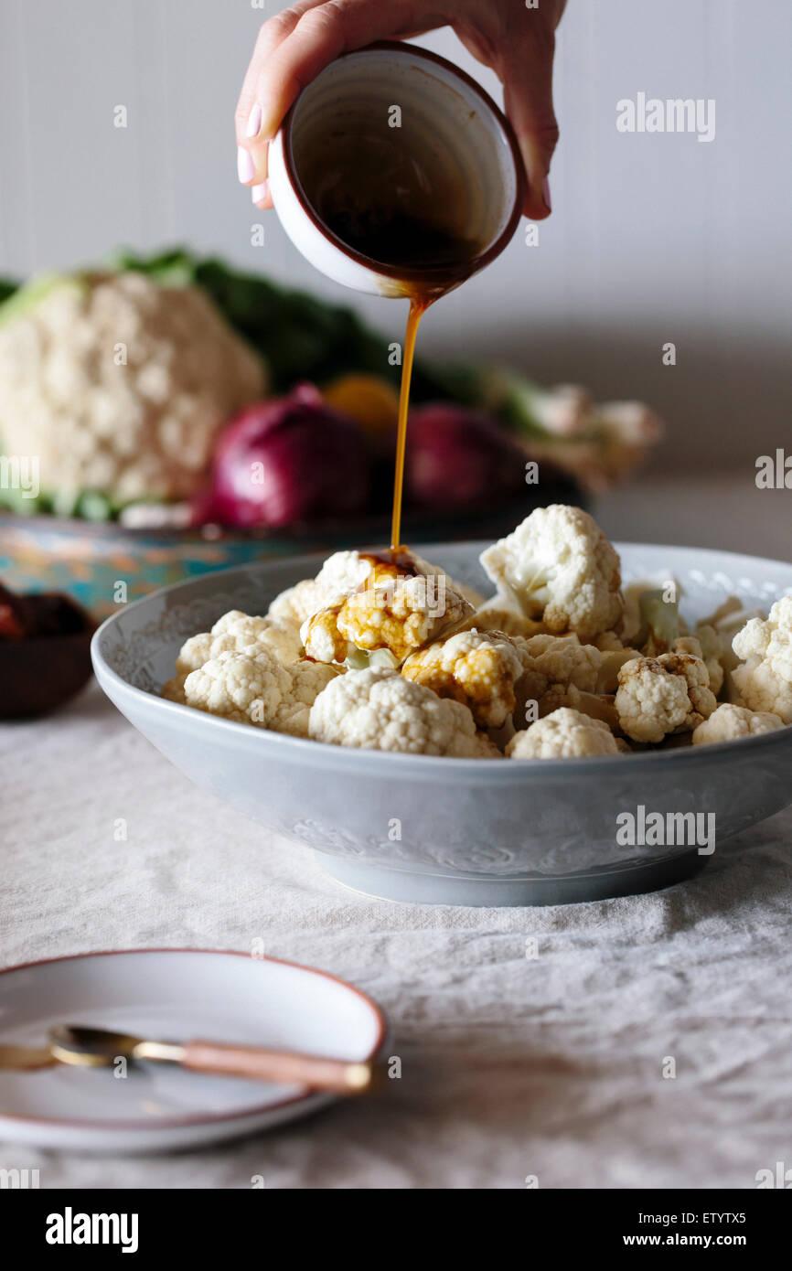 Floretes de coliflor Raw están siendo rociados con un aderezo picante por una persona. Imagen De Stock