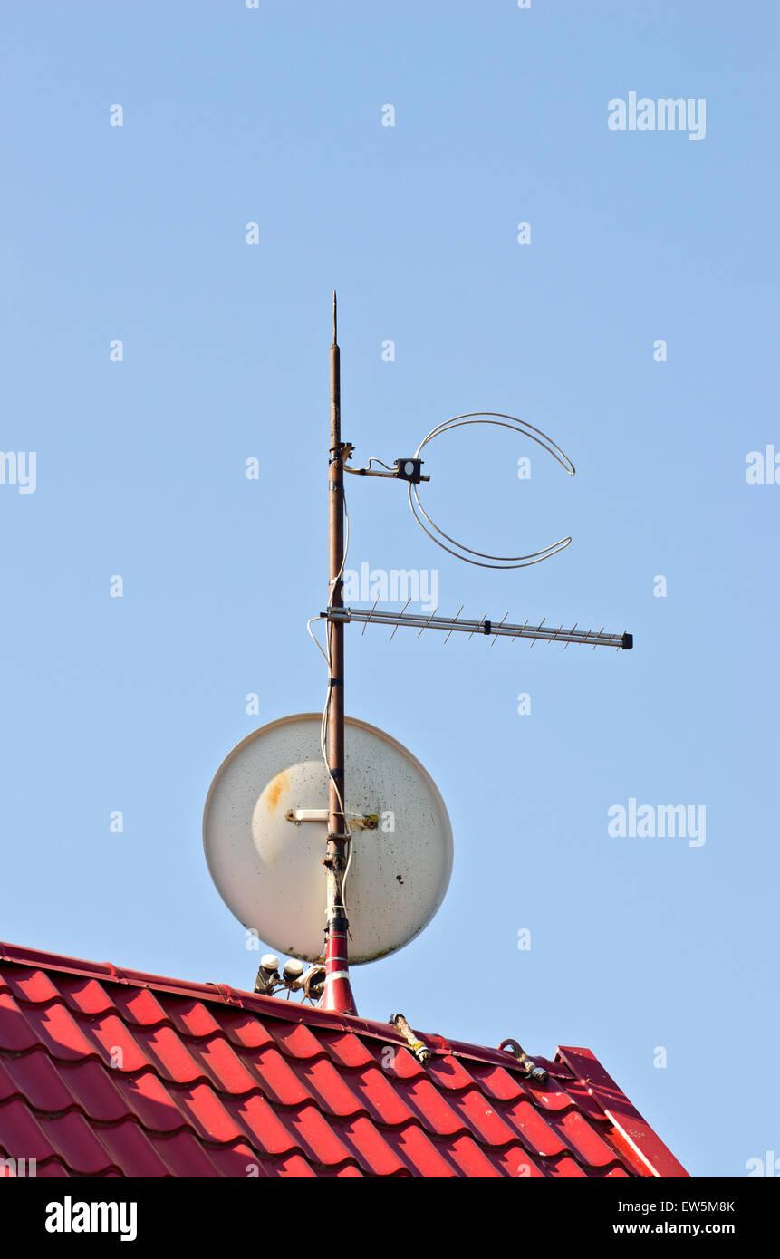 Antena de televisión satelital en nuevos azulejos de techo rojo Foto de stock