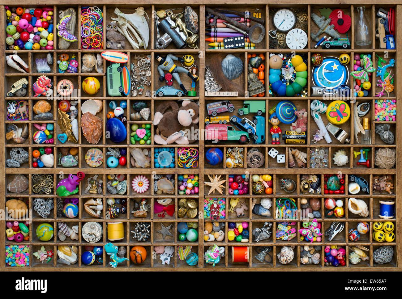 Bandeja de madera de juegos infantiles y un tesoro de pequeños elementos coleccionables Foto de stock