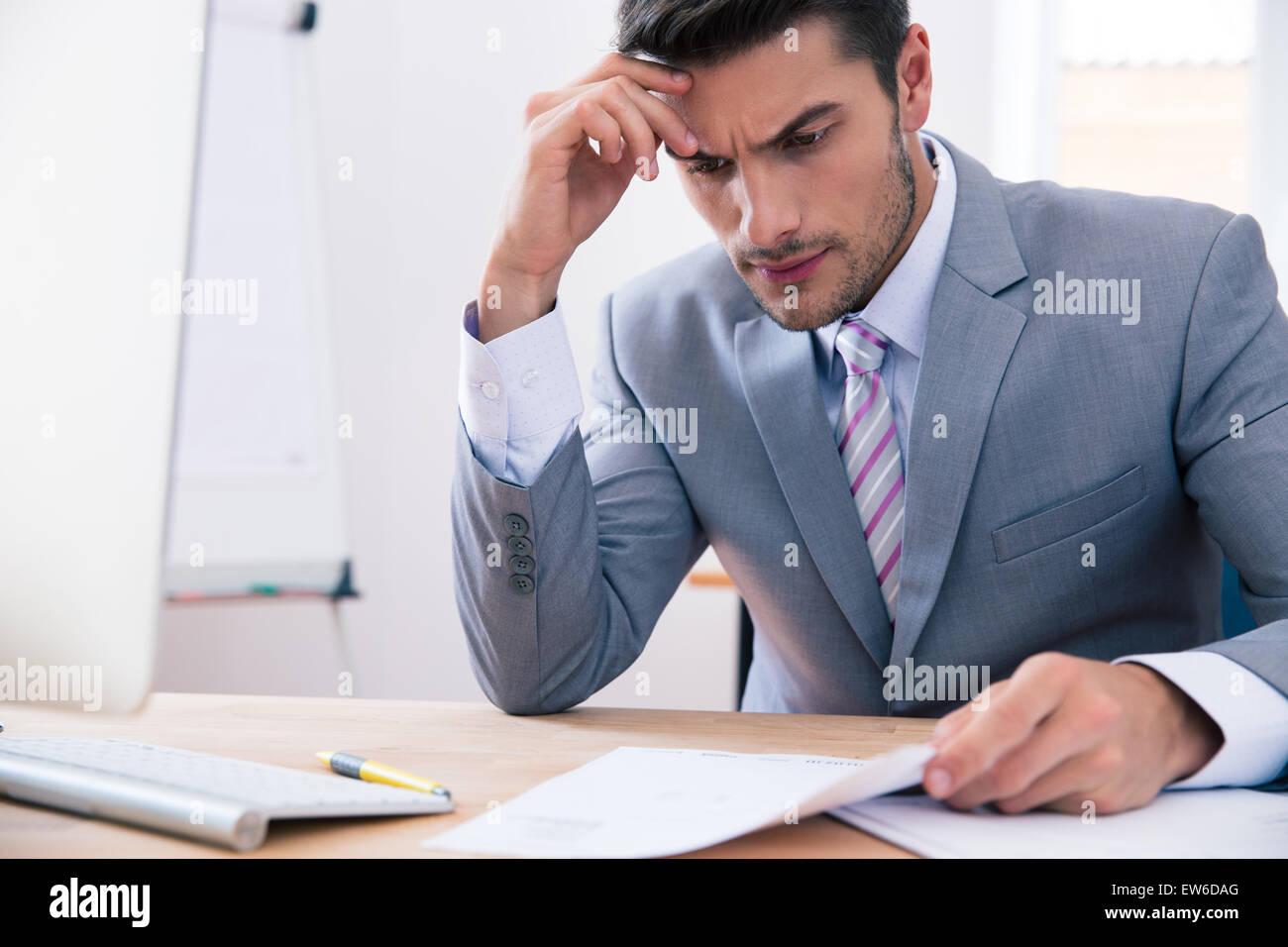 Guapo empresario sentado a la mesa en la oficina y leer el documento Imagen De Stock
