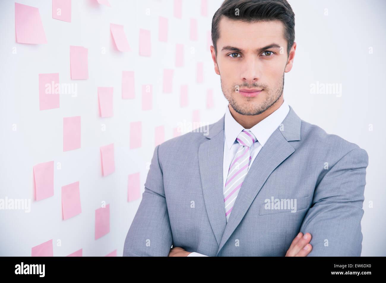 Apuesto joven empresario de traje en la oficina permanente y mirando a la cámara Foto de stock