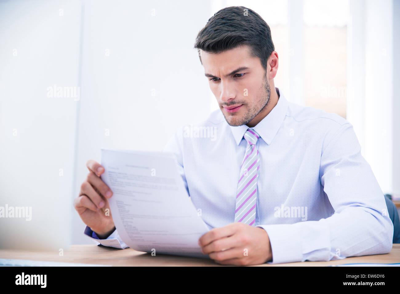 Guapo empresario sentado a la mesa leyendo documento en Office Imagen De Stock
