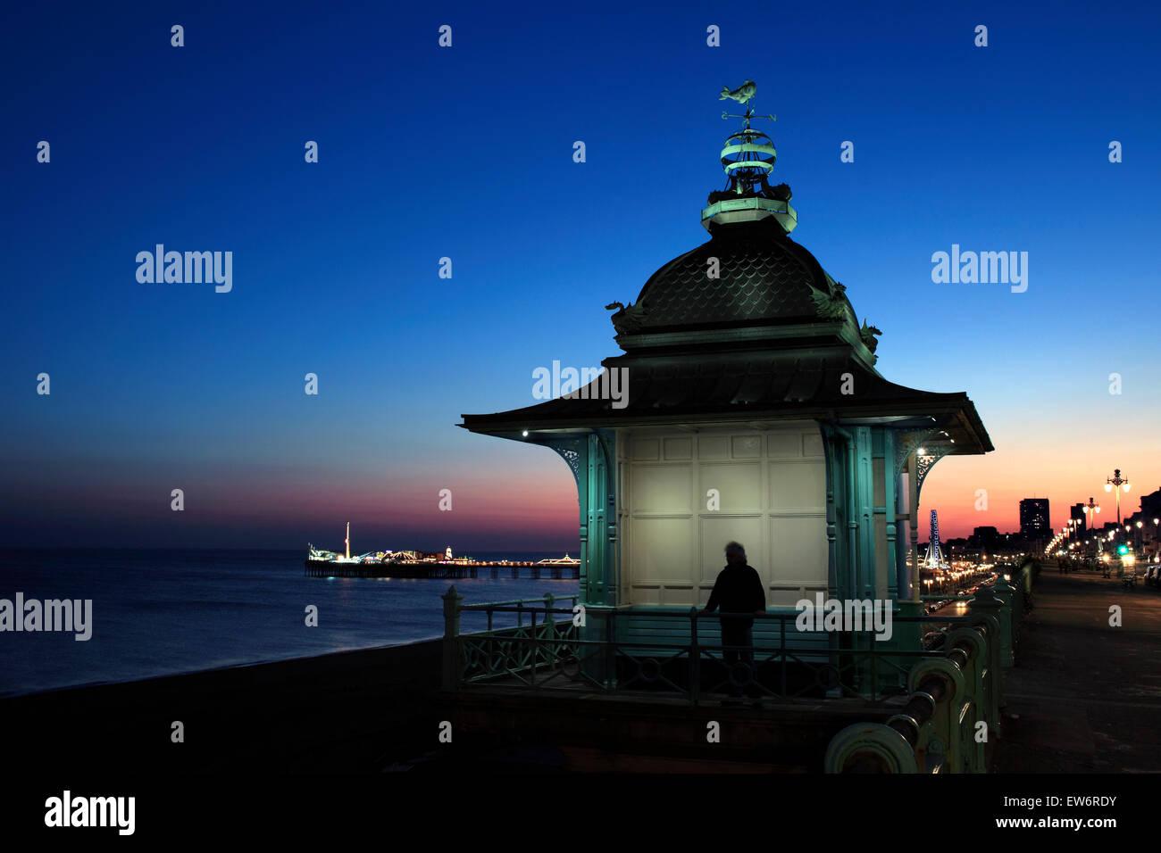 Cielo crepuscular detrás del elevador de madeira, Marine Parade, Brighton Pier iluminada en el fondo. Imagen De Stock