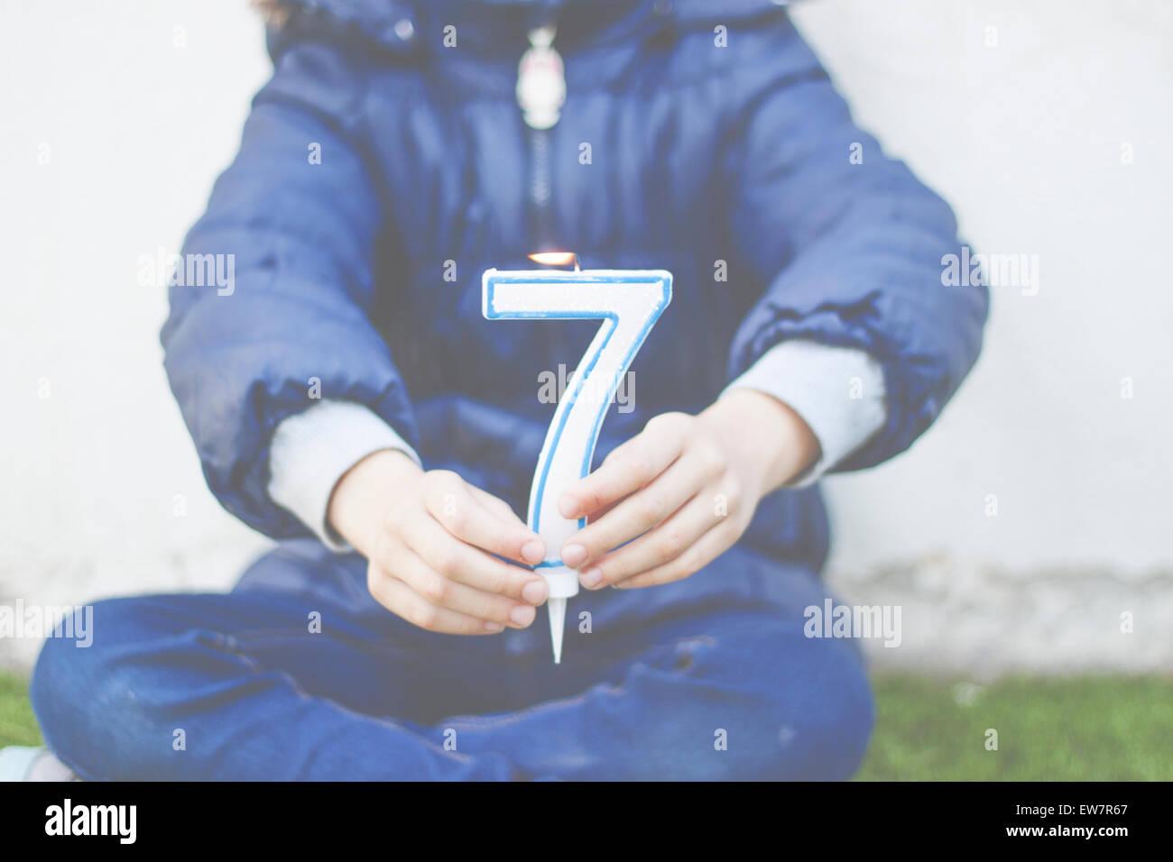 Chica sentada piernas cruzadas sosteniendo un número siete velas Imagen De Stock