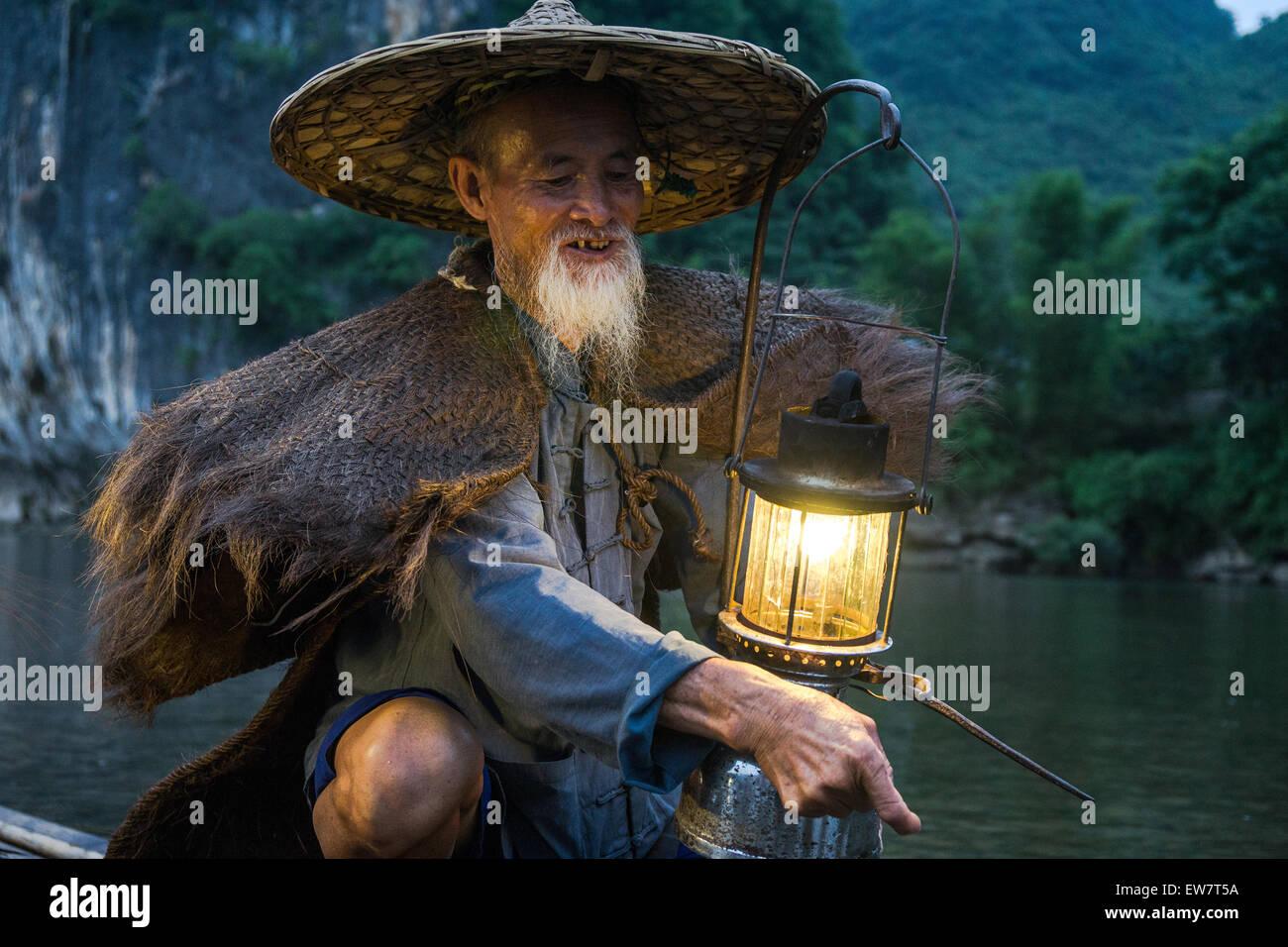 Retrato de un viejo pescador chino con linterna en barco de bambú Imagen De Stock