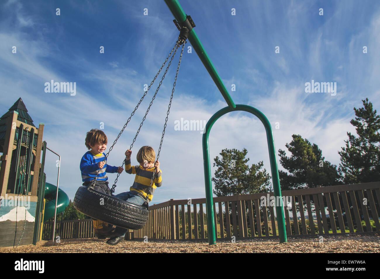 Dos muchachos balanceándose en un columpio de neumático en un parque Imagen De Stock