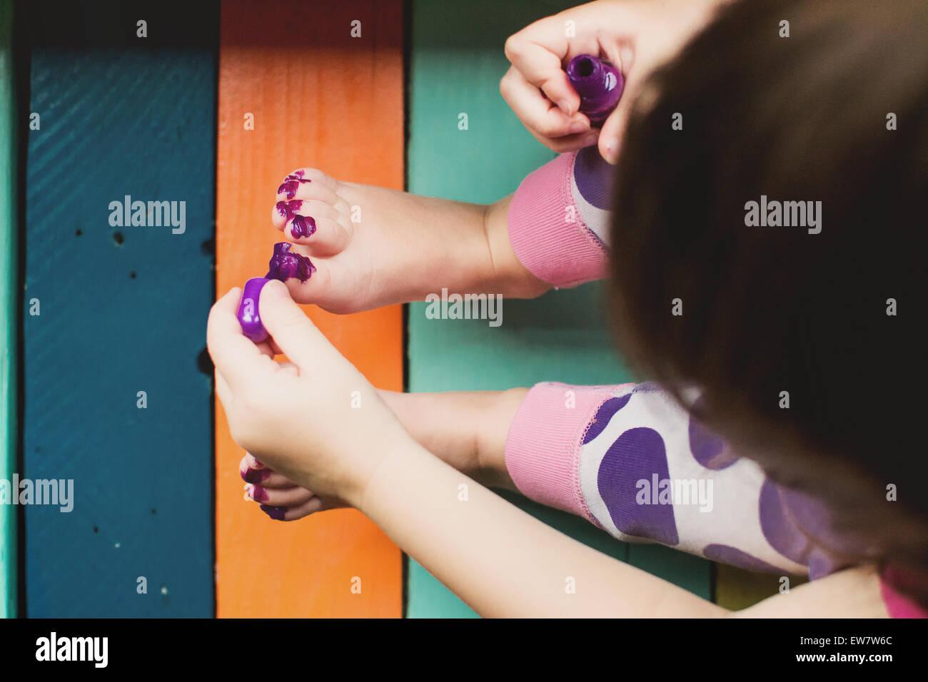 Vista elevada de una niña messily pintando sus dedos Imagen De Stock