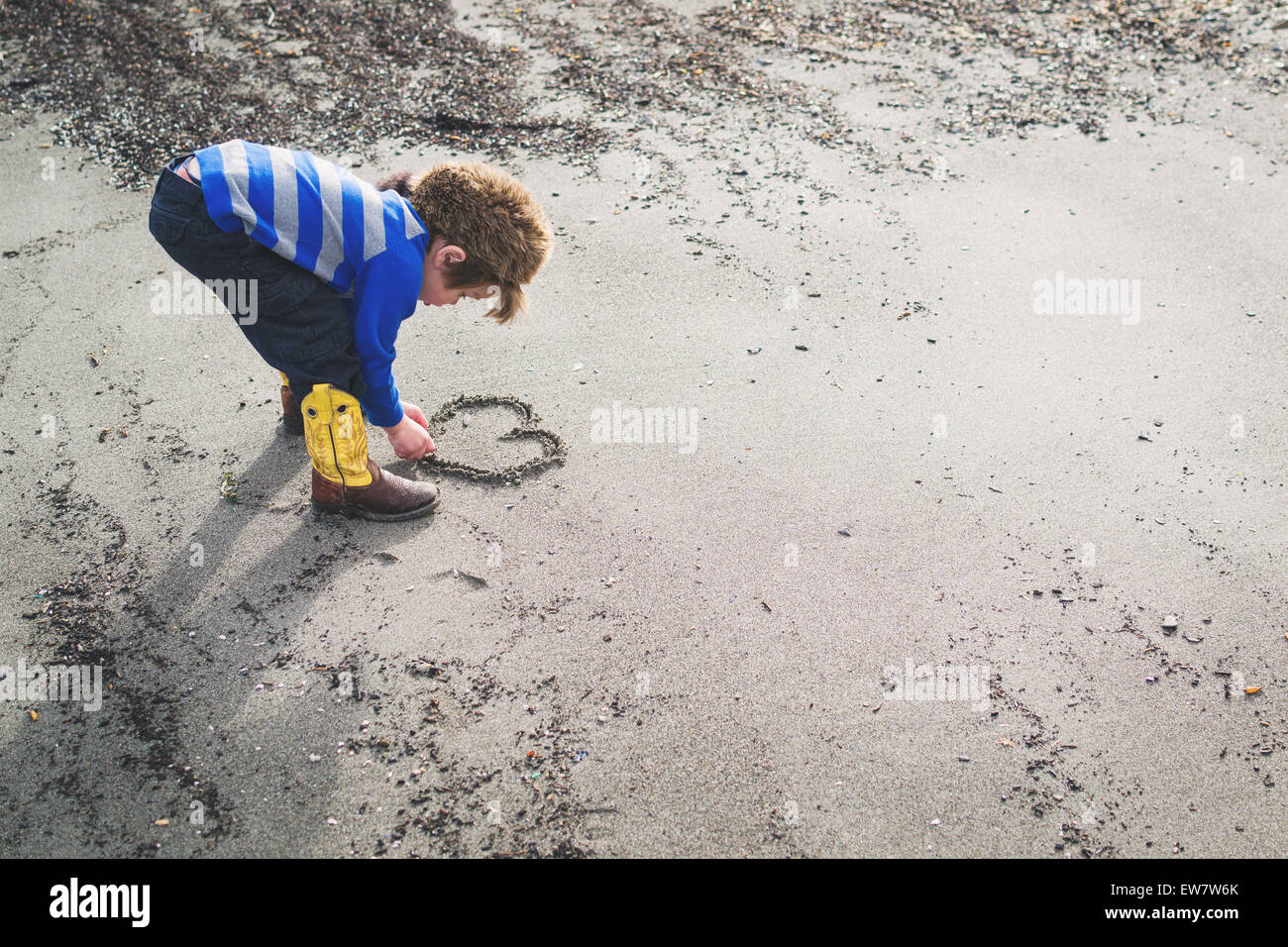 Chico en botas vaqueras y Sombrero de mapache dibujando un corazón en la arena Imagen De Stock