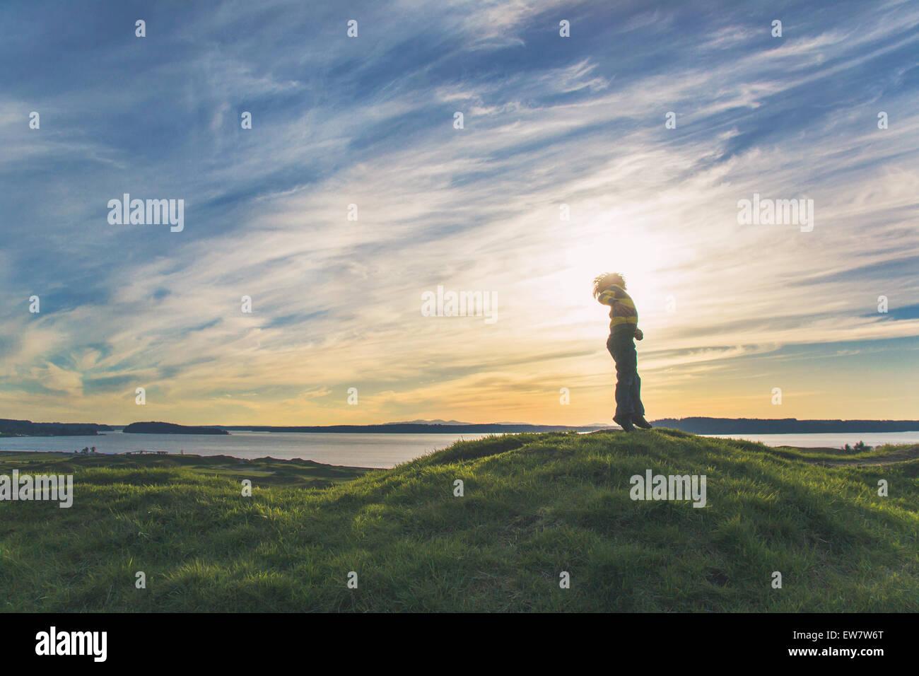 Ángulo de visión baja de un muchacho saltando sobre una colina Foto de stock