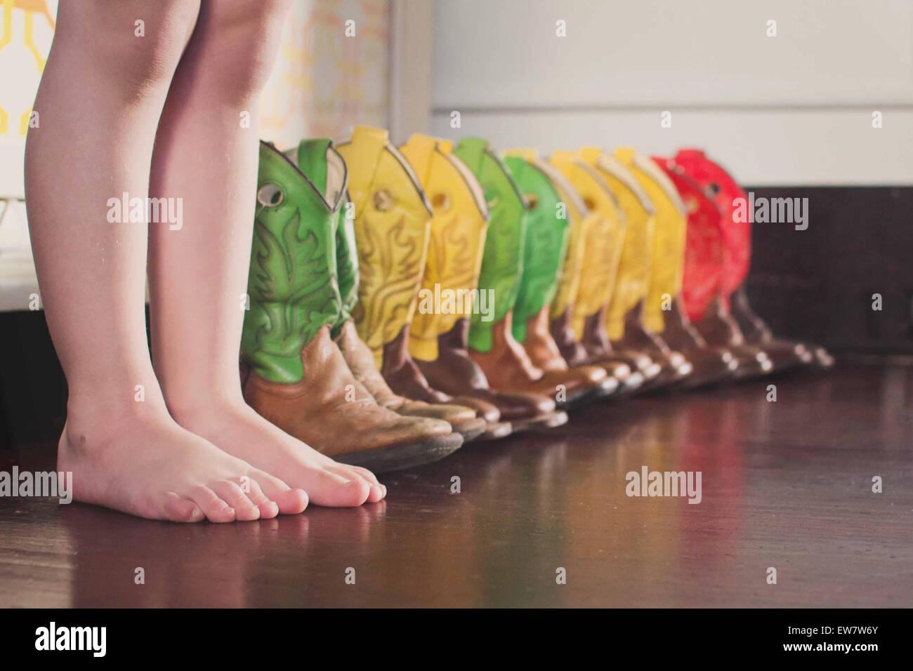 Niño de pie junto a una fila de coloridas botas vaqueras Imagen De Stock