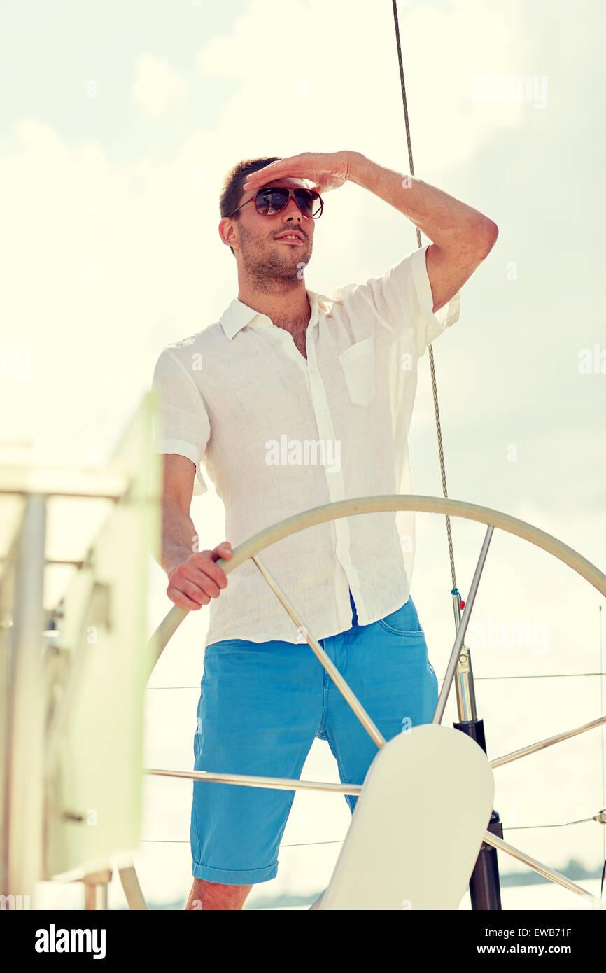 Joven en gafas de sol el volante en velero Imagen De Stock