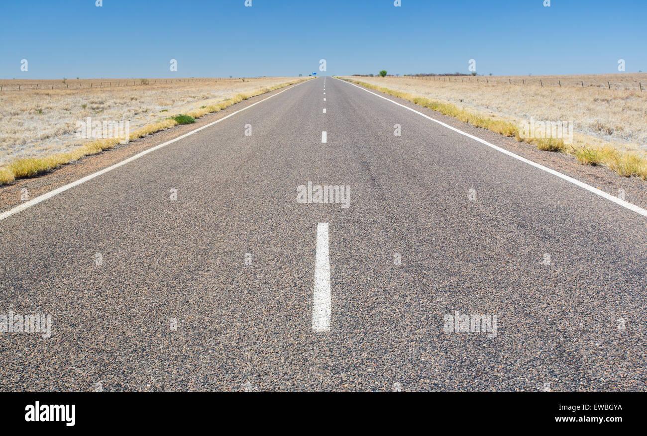 Autopista en carretera abierta, país árido outback, Queensland, Australia Foto de stock