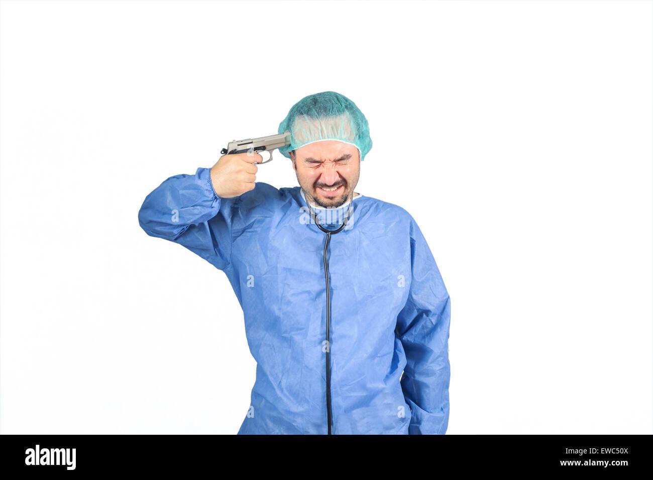 Cirujano planeando el suicidio, la pistola en la cabeza ojos cerrados aislados sobre fondo blanco. Imagen De Stock