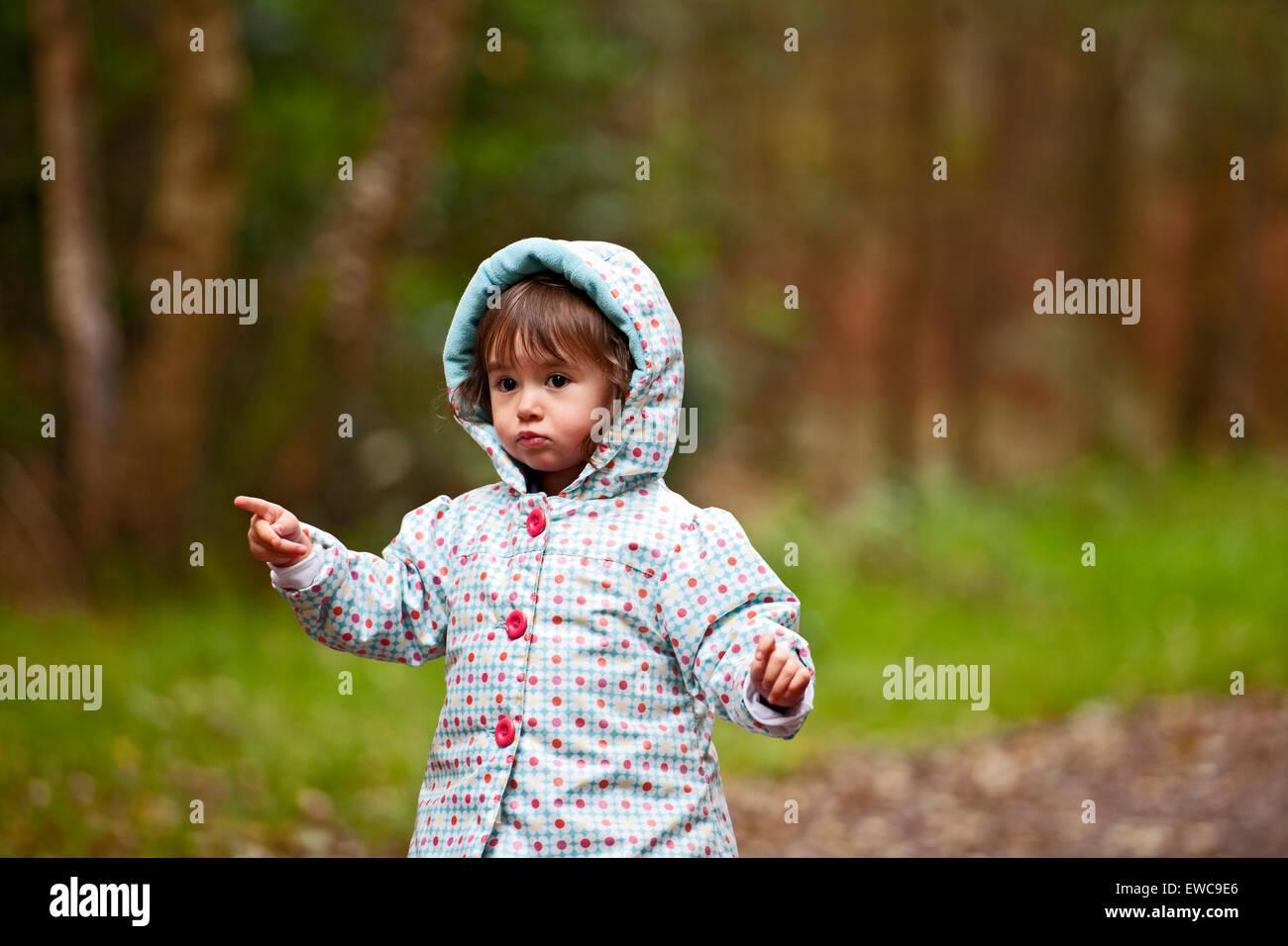 La niña de etnicidad mixta caminando a través de un frondoso Imagen De Stock