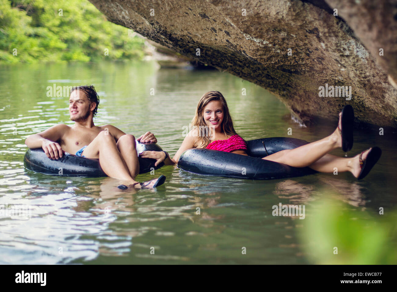 Una joven pareja tubos abajo de un río. Imagen De Stock