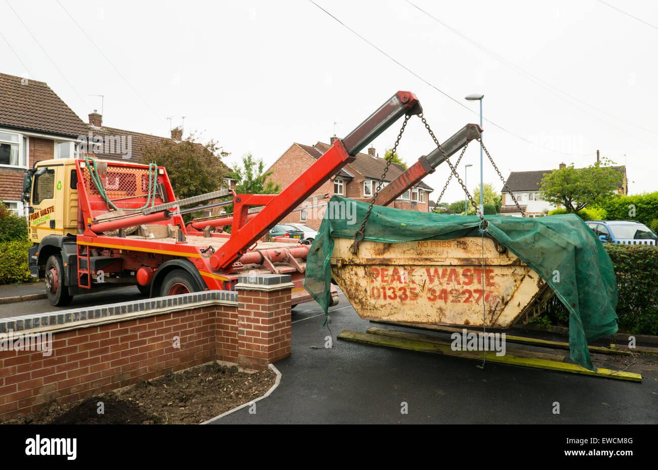 Un completo +residuos cubiertos skip recopilados por camión a una constricción de suburban cochera Derby Imagen De Stock
