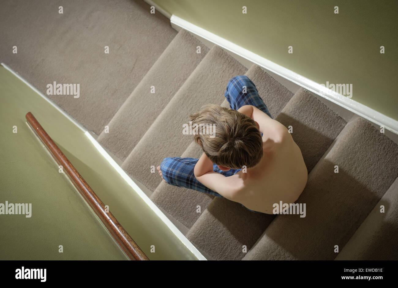 Un niño sentado en las escaleras con su cabeza en sus manos mirando disgustado Imagen De Stock