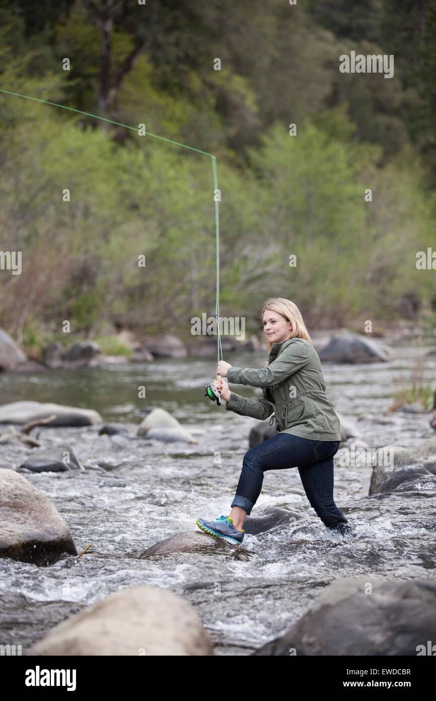 Una joven mujer de aventura, la pesca con mosca en el actual movimiento rápido del río Feather, en las Imagen De Stock
