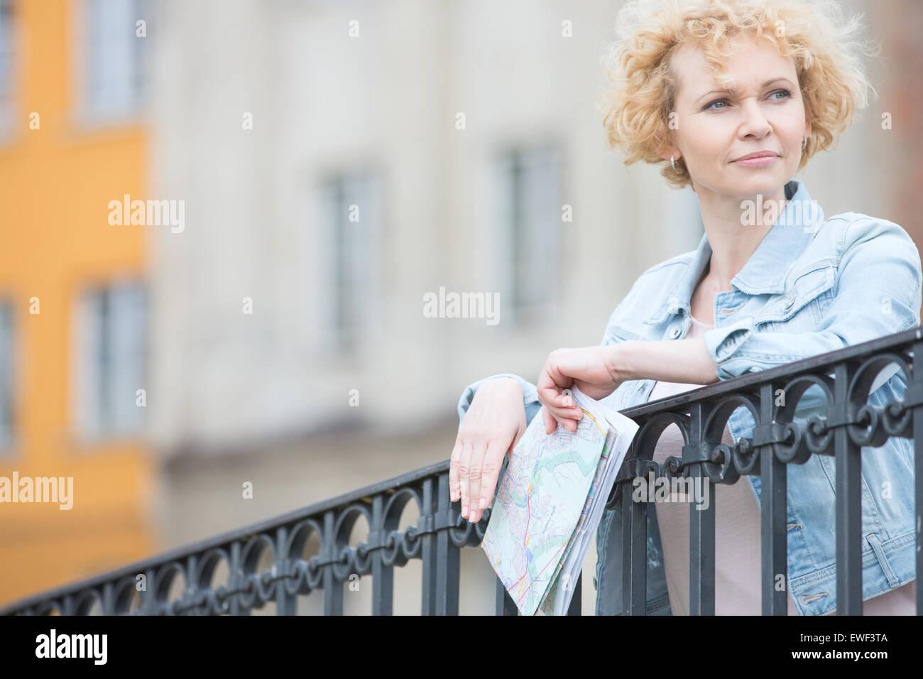 Pensativo mujer de mediana edad celebración mapa mientras recostado en la baranda Imagen De Stock