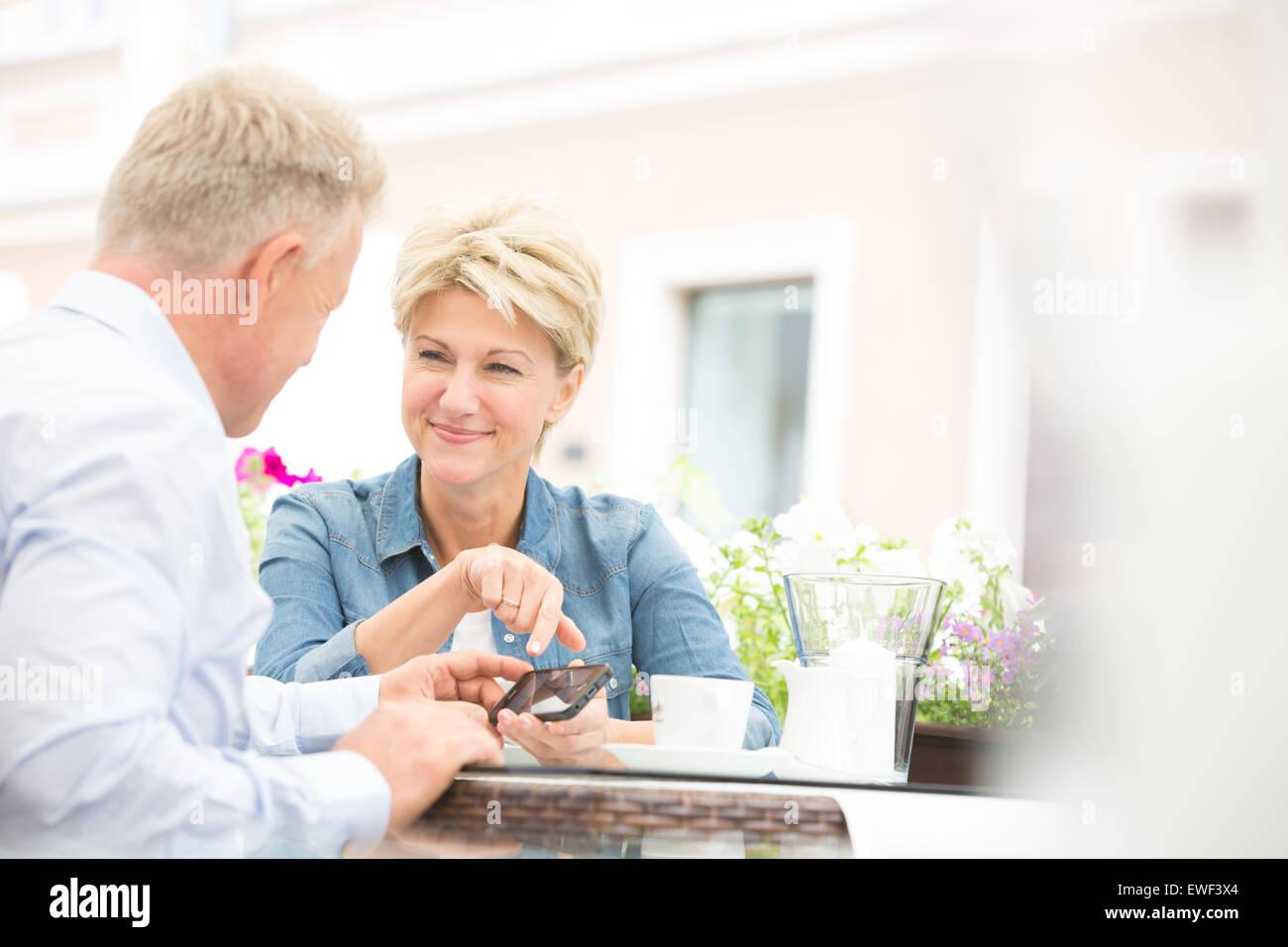 Feliz pareja de mediana edad con celular en la cafetería Foto de stock