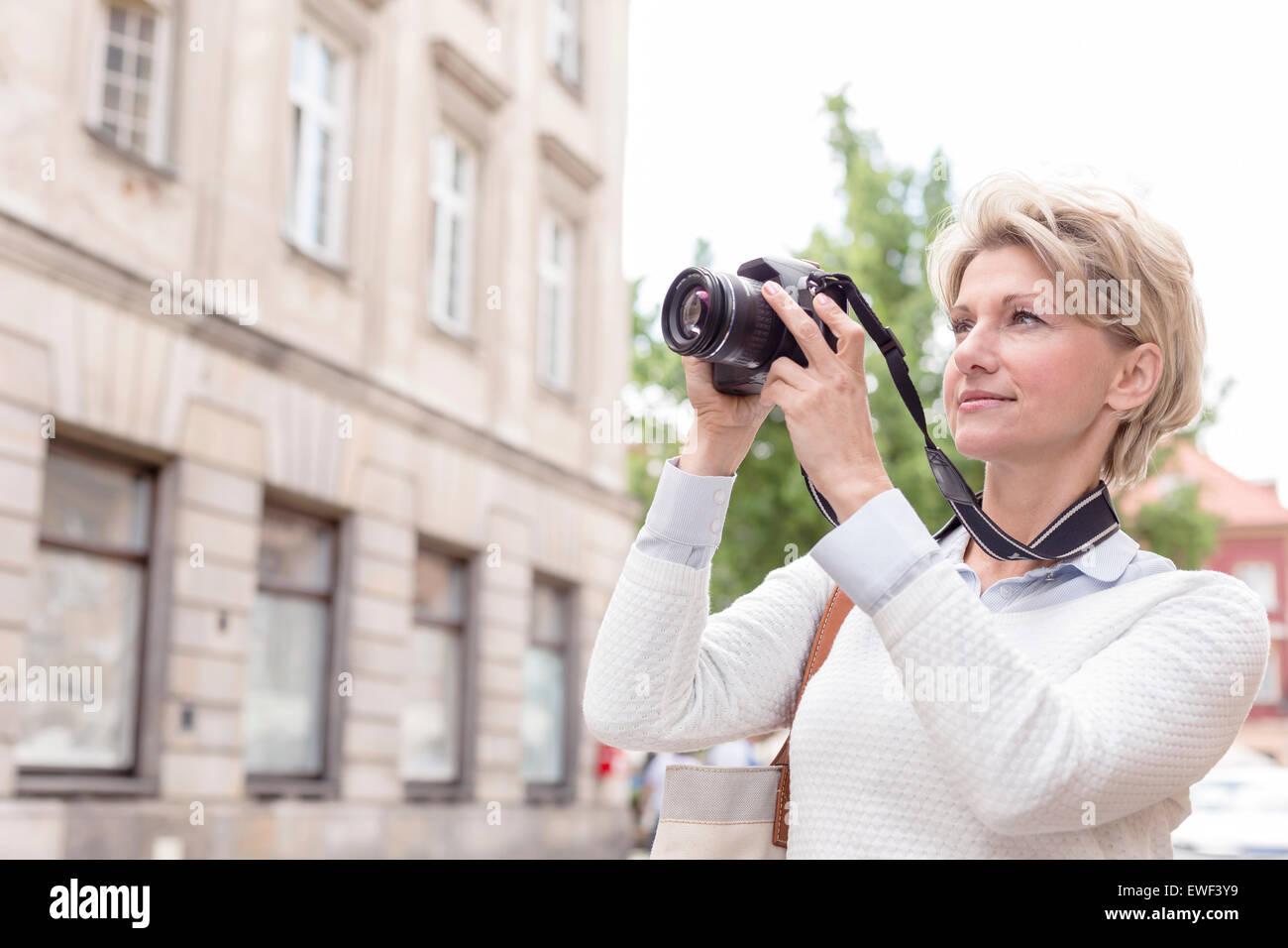 Mujer de mediana edad fotografiar a través de una cámara digital en la ciudad Imagen De Stock
