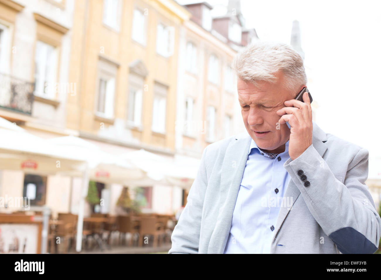 Hombre de mediana edad a través de teléfono móvil en la ciudad Imagen De Stock