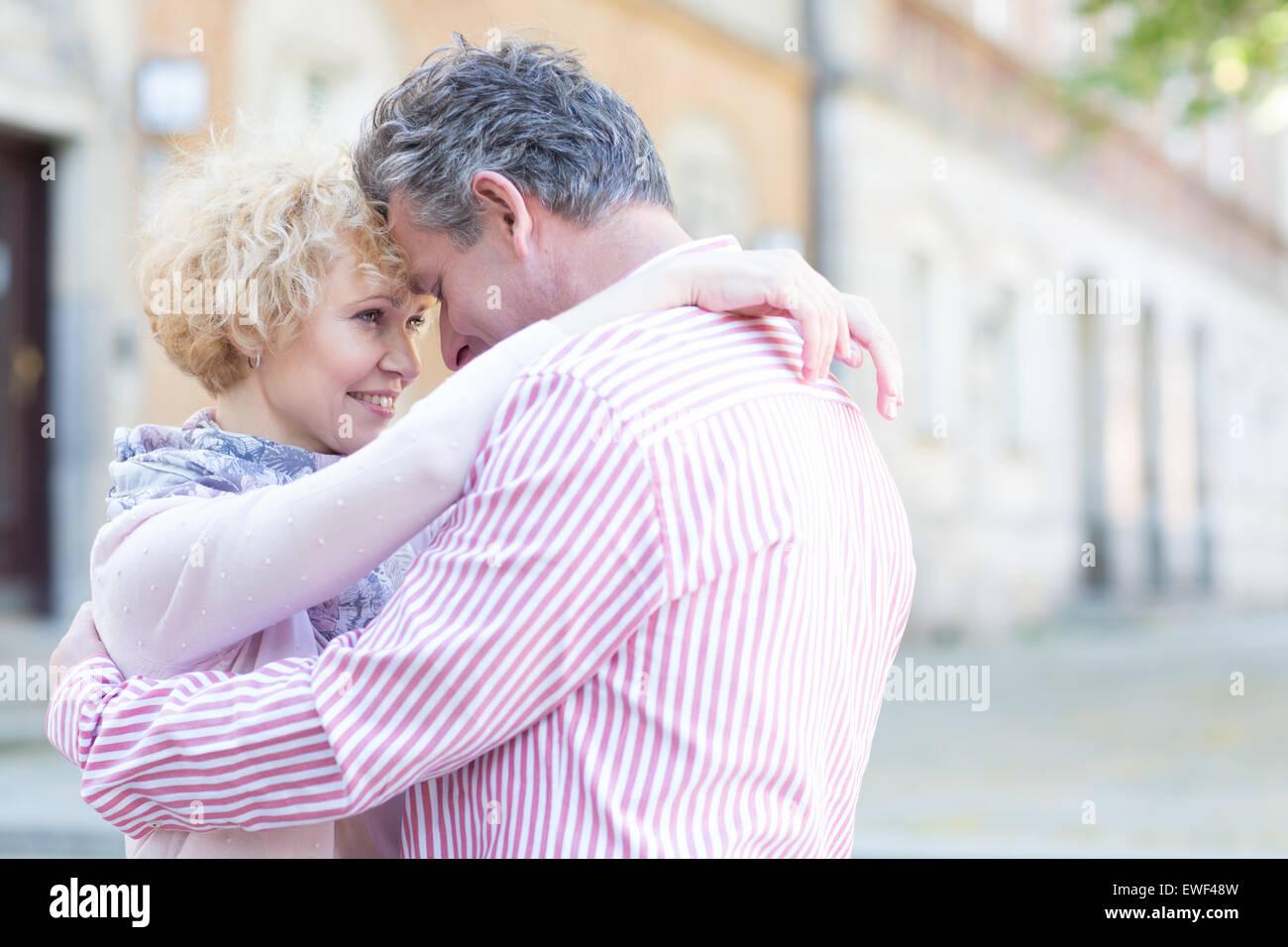 Feliz pareja abrazada de mediana edad en ciudad Foto de stock