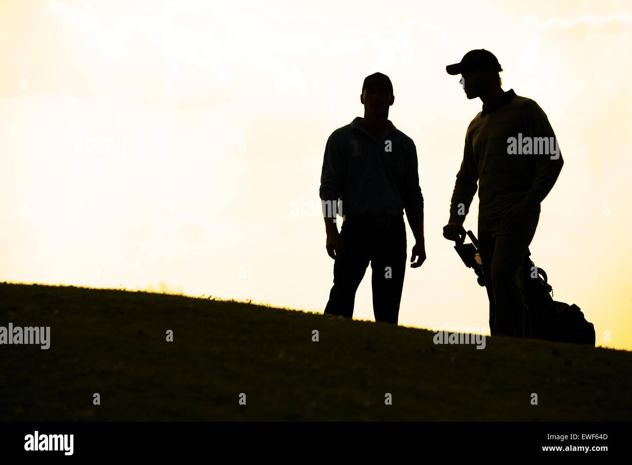 Silueta de jóvenes parados en campo de golf con carrito Imagen De Stock