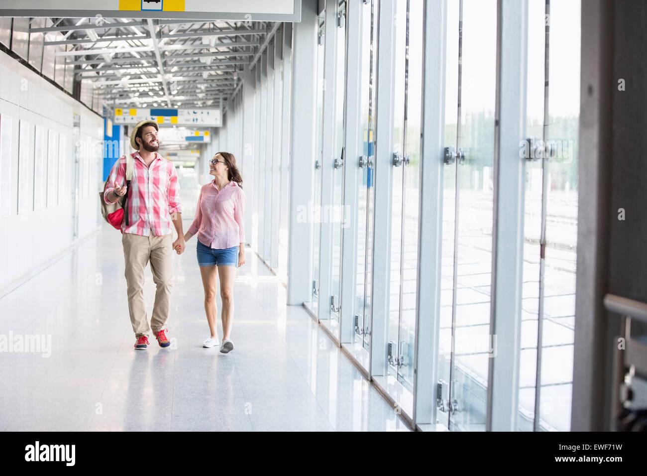 La longitud completa de la pareja caminando en pasaje cubierto Foto de stock