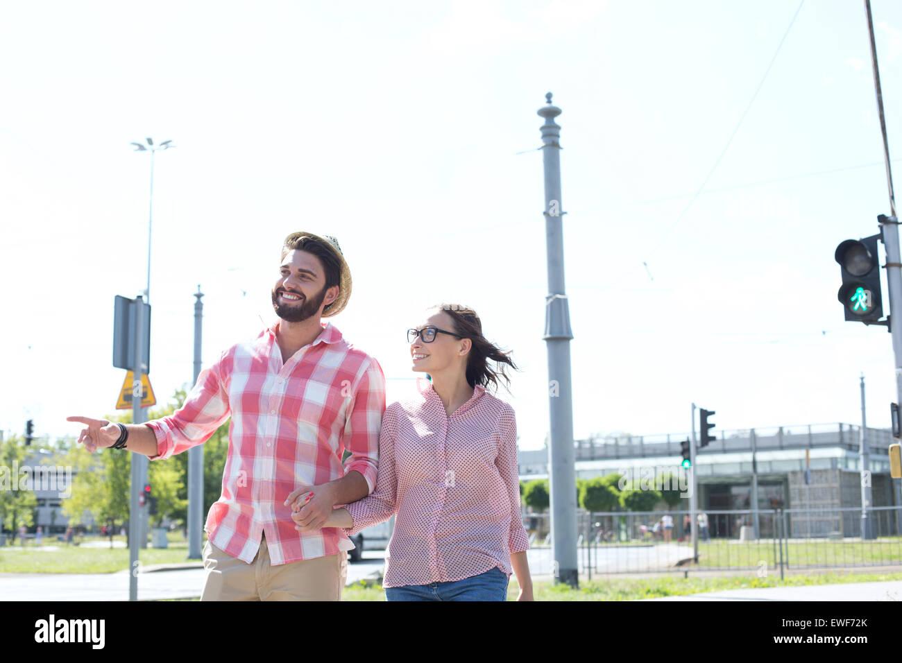 Feliz pareja caminando en la ciudad contra el cielo claro Imagen De Stock