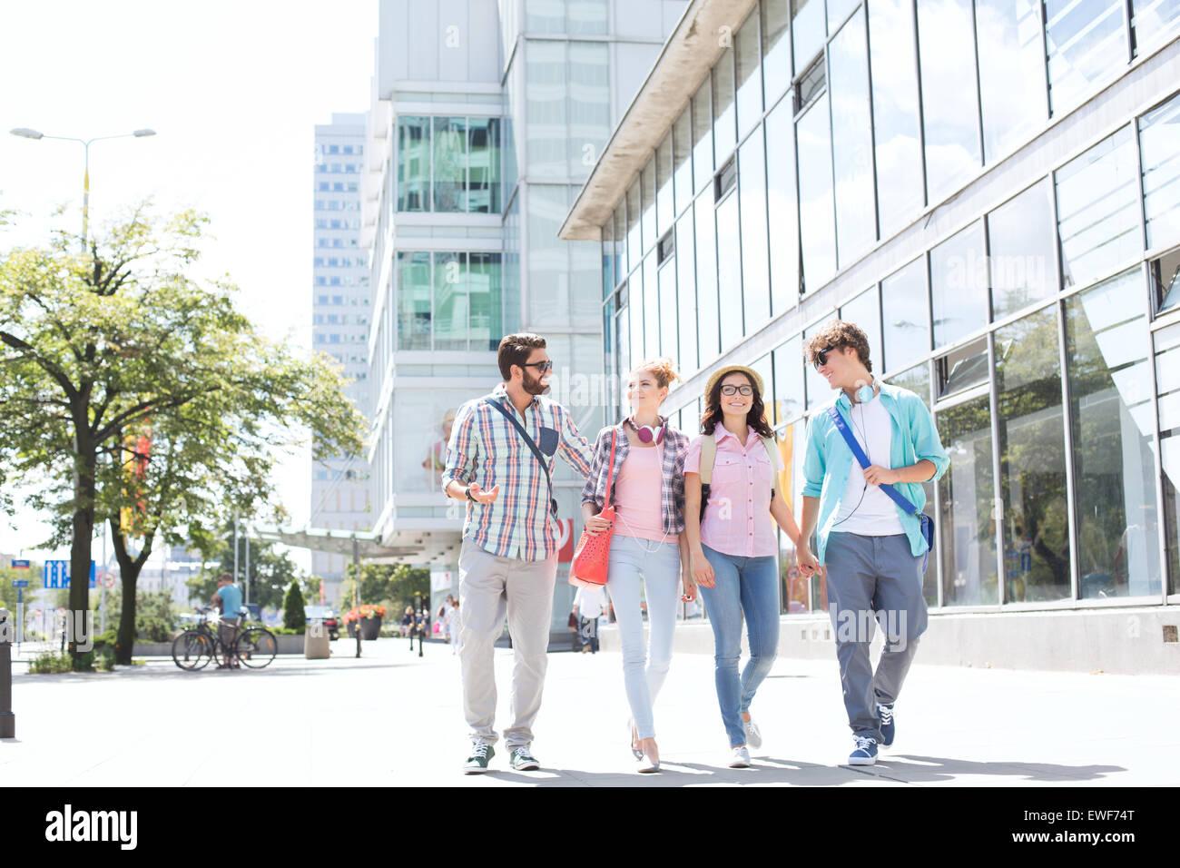 De longitud completa amigos masculinos y femeninos caminando por las calles de la ciudad Imagen De Stock