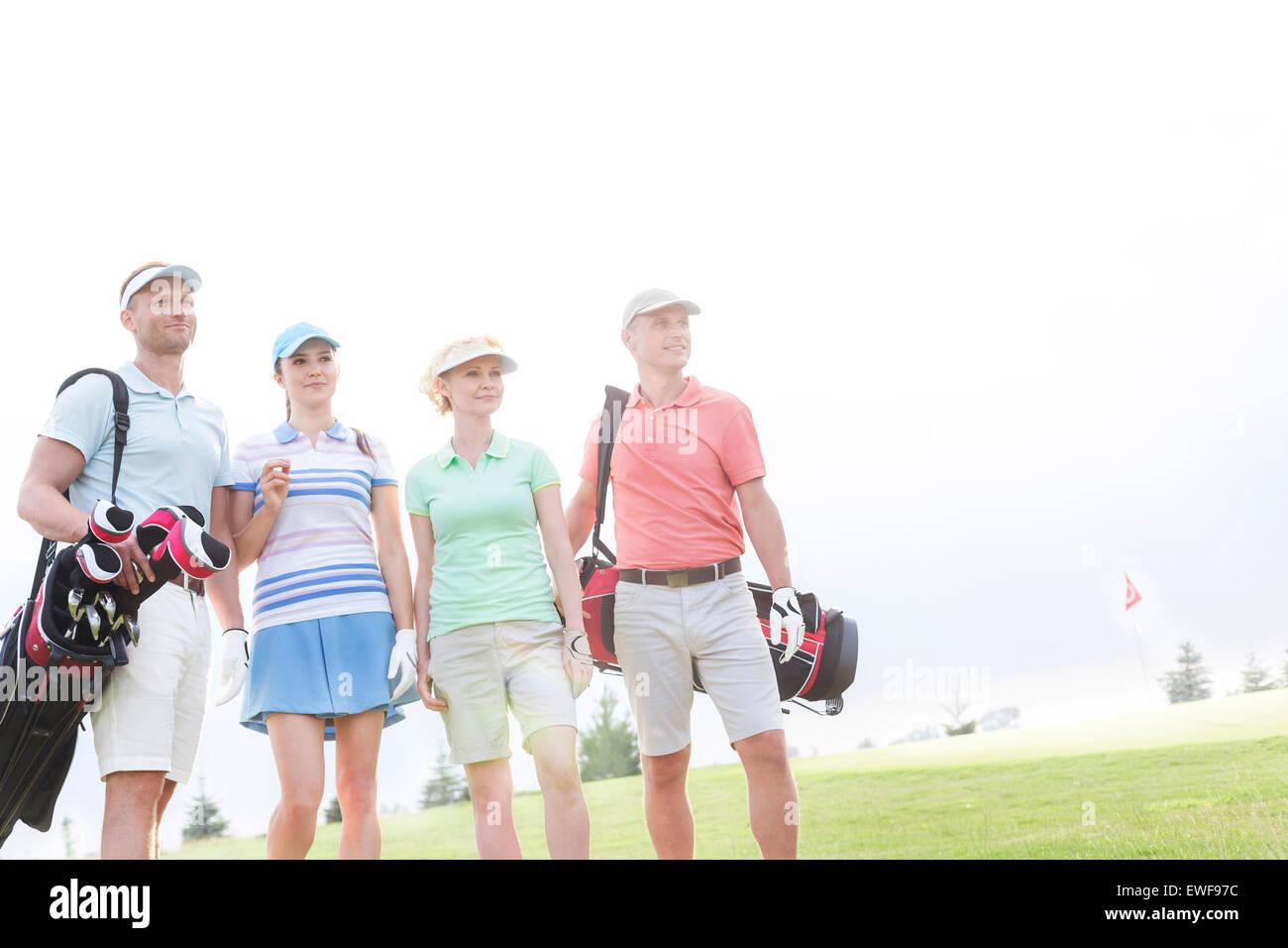 Amigos masculinos y femeninos de pie en el campo de golf contra el cielo claro Imagen De Stock