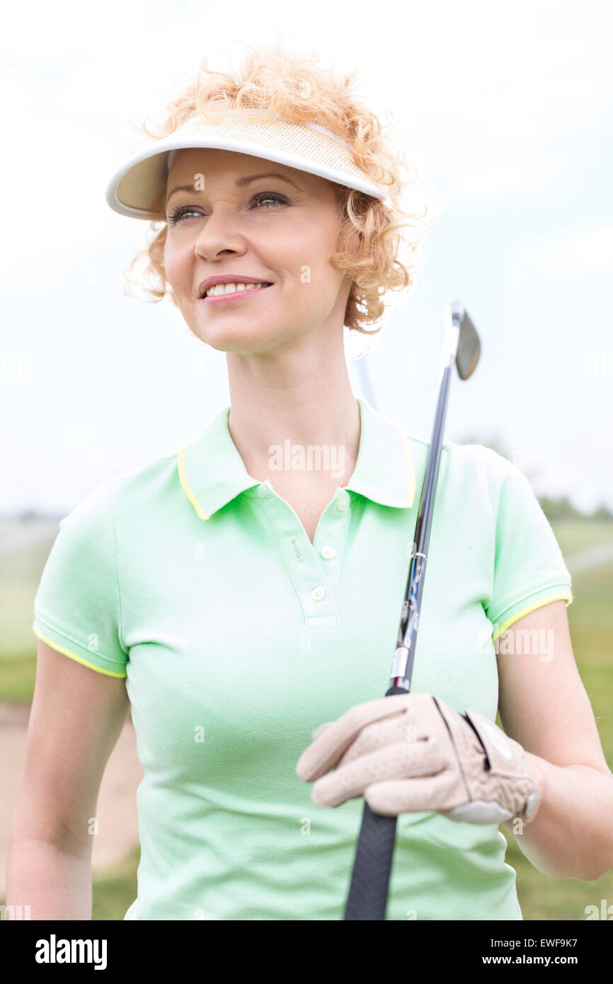 Mujer de mediana edad pensativa mirando a otro lado mientras mantiene golf club Imagen De Stock