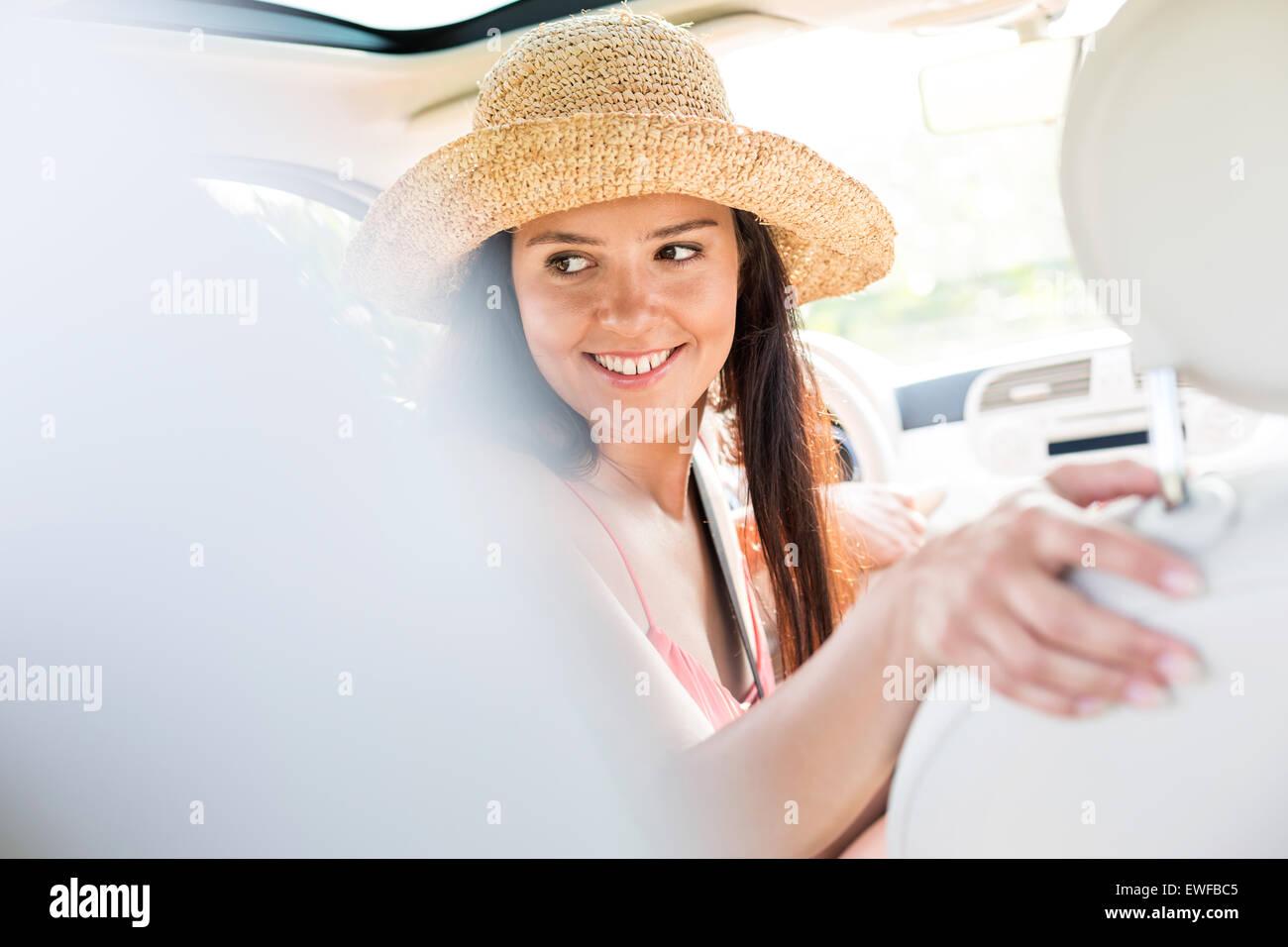 Feliz mujer mirando hacia atrás durante la conducción de automóviles Imagen De Stock