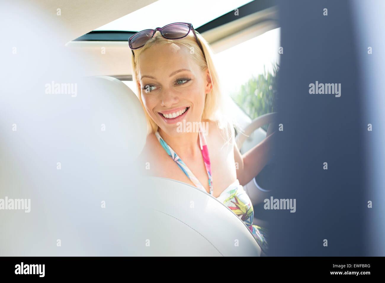Feliz hermosa mujer mirando hacia atrás, mientras que la conducción de automóviles Imagen De Stock