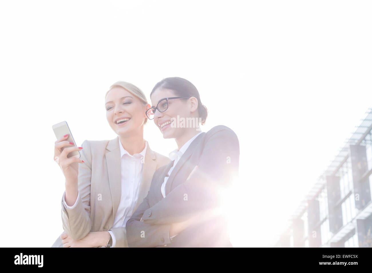 Ángulo de visión baja de feliz empresarias mediante teléfono inteligente contra el cielo claro en Imagen De Stock