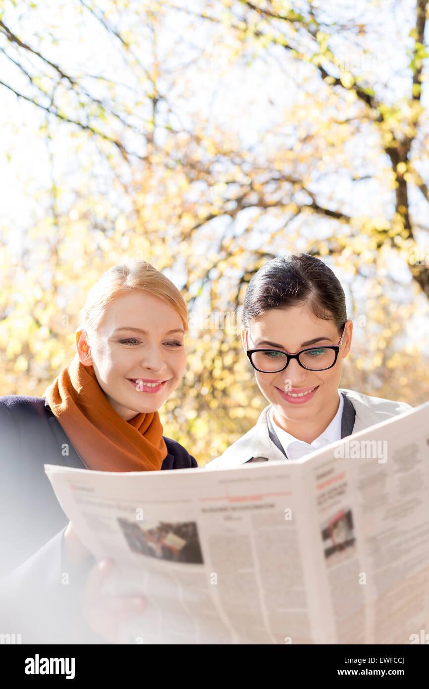 Feliz lectura de periódicos de empresarias en park Imagen De Stock