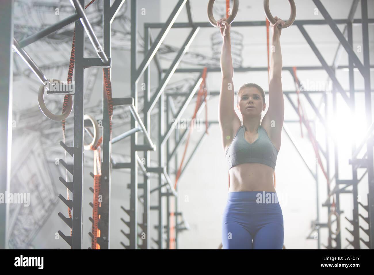 Seguros de la mujer ejerce con anillos de gimnasia en el gimnasio crossfit Imagen De Stock