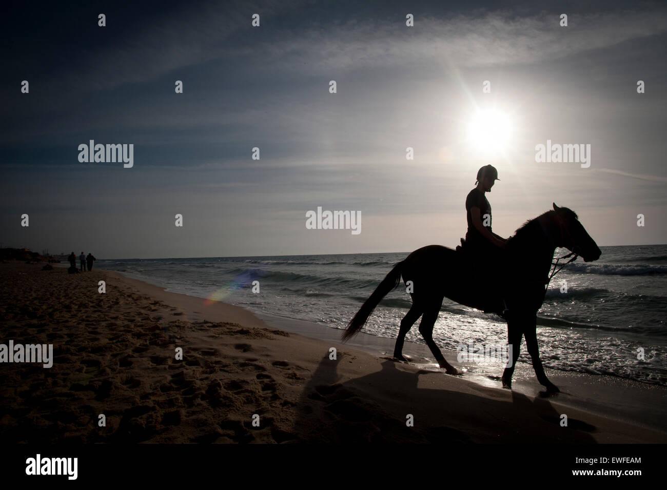 Montando a caballo en la playa, en la Franja de Gaza, territorio palestino ocupado. Imagen De Stock