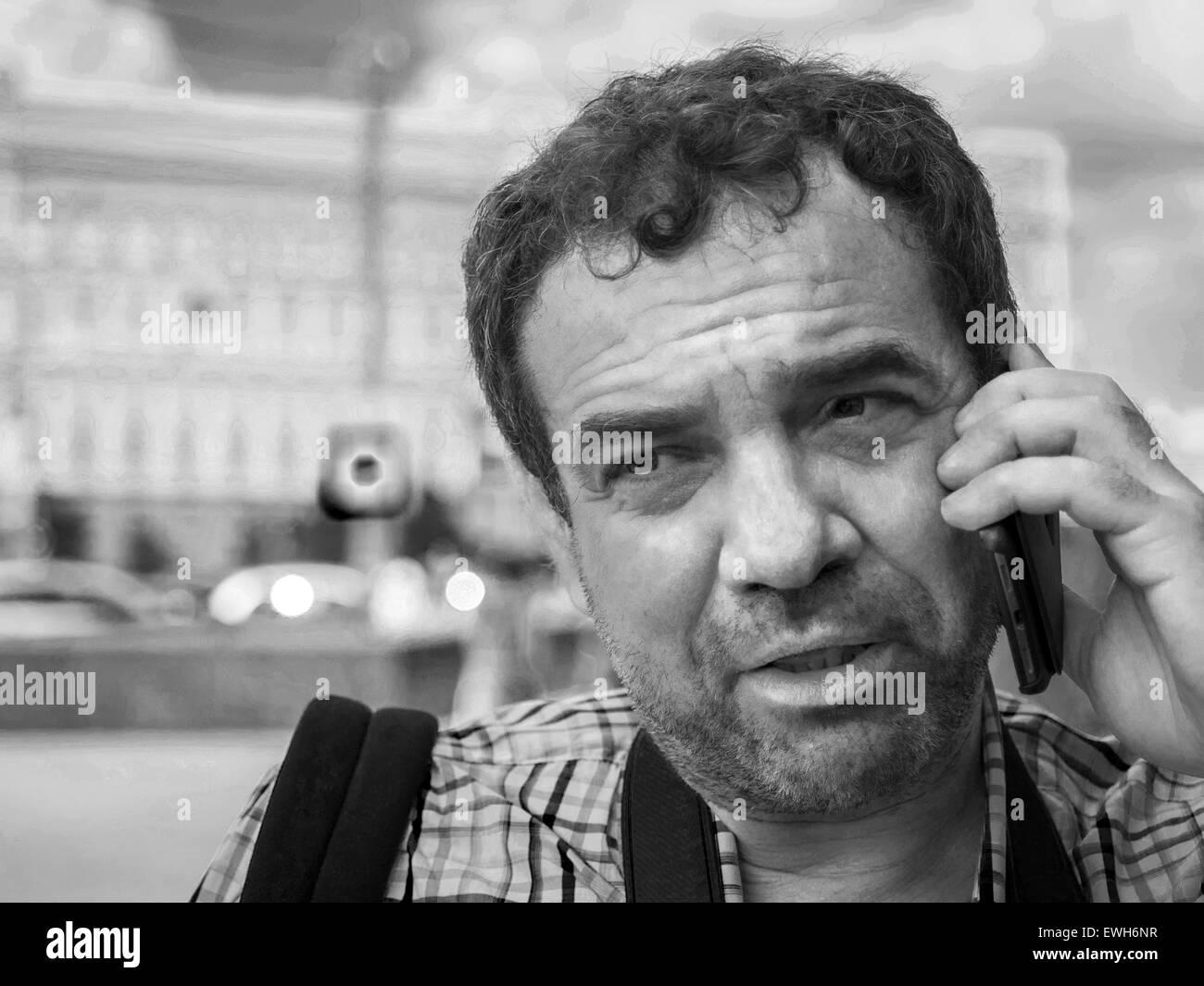 Junio 14, 2015 - Hombre en camisa de manga corta hablando por teléfono en la calle. (Crédito de la Imagen: Imagen De Stock
