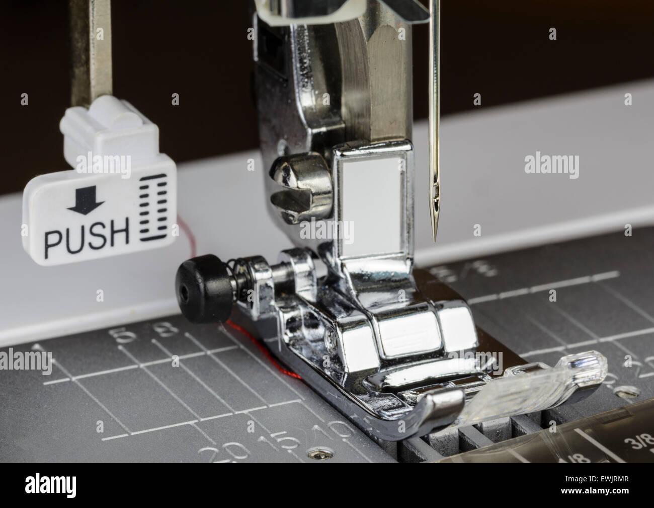 Prensatelas. Acercamiento de los prensatelas y la aguja de una máquina de coser eléctrica. Imagen De Stock