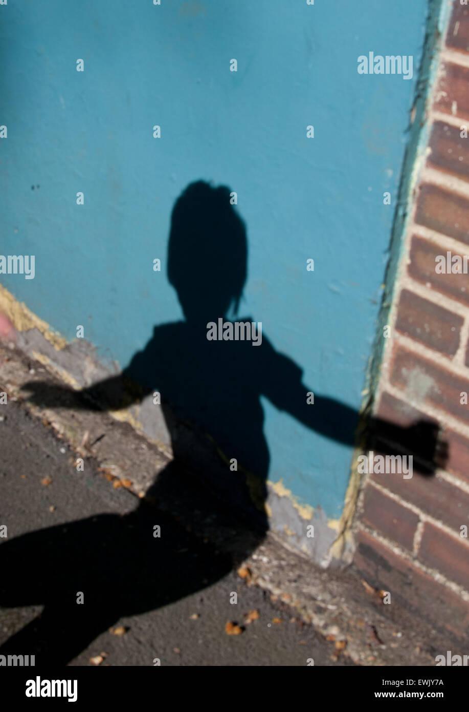 Sombra del muchacho en la pared Foto de stock