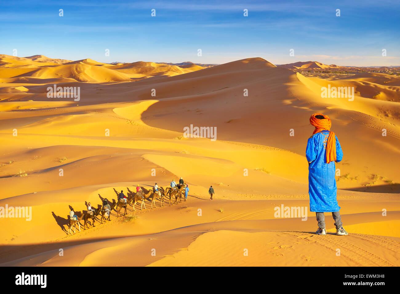 Hombre mirando bereber caravana de camellos, Erg Chebbi : desierto cerca de Merzouga, Sahara, Marruecos Imagen De Stock