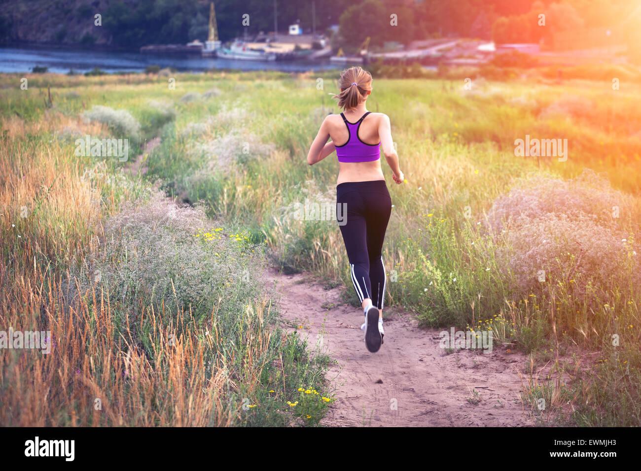 Mujer joven corriendo en un camino rural al atardecer en el verano del campo. Antecedentes deportivos en el estilo Imagen De Stock
