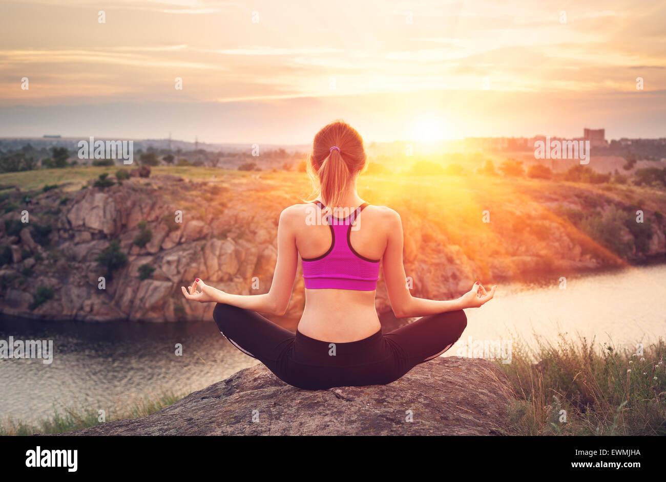 Mujer joven practicando yoga en la colina al atardecer cerca del río. Imagen De Stock