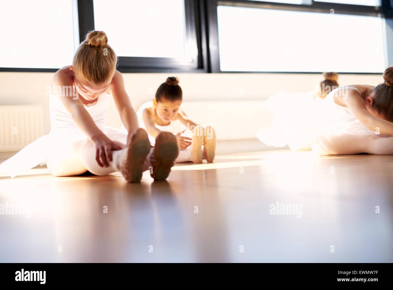 Poco ballet chicas haciendo una sentada y alcanzar el ejercicio de calentamiento para estirar el cuerpo dentro del Imagen De Stock